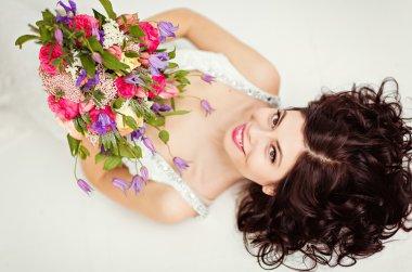 Portrait of beautiful brunette girl in a white fishnet dress wit