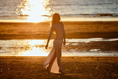 Beautiful long-haired skinny girl in a long skirt walks along th