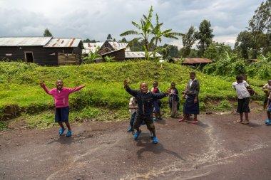 children waving in dirty road inside Virunga