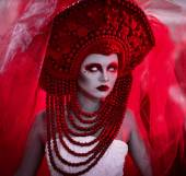 Fotografie Wedding in red colors, bride in red veil, corona, red makeup and white linces,serious look,white long dress.Creative closeup portrait of fashionable bride,model,girl,woman and strong,serious,angry,dangerous evil look,eyesight on the black background