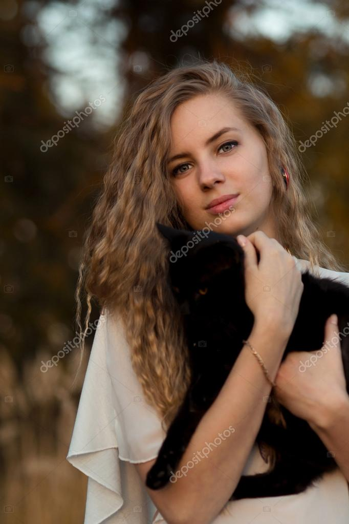 Nice girl with her favourite pet - black cat.Beautiful happy smiling blonde girl hold black cat in hands.Cute girl with long curly hair hug little, ...
