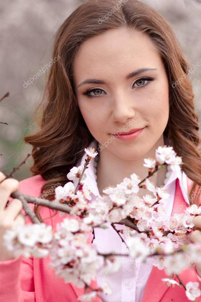 Very beautiful girl in blossoming trees in spring garden.Spring time.Very pretty,awesome,gorgeous,nice girl with perfect hairstyle,pink jacket in spring blossoming park with many white flowers.Cute.