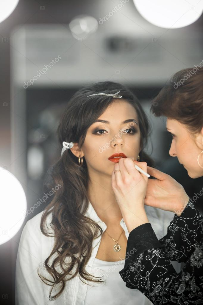 Professional makeup artist makes up lips beautiful,attractive model,celebrity.Beautiful,fashionable,glamorous,famous,nice,attractive,pretty,sexy celebrity,model,lady,girl,woman prepare for shooting.Nice face,pure,clean skin.Cosmetics.Salon.Profession