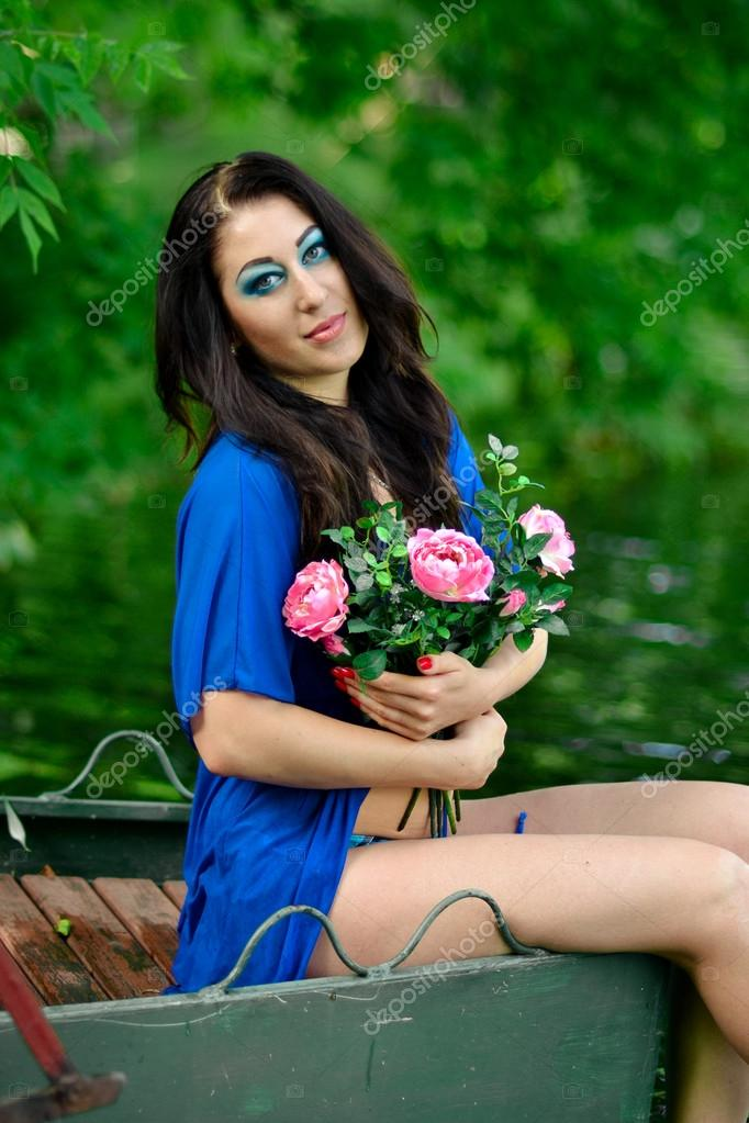 .Beautiful girl with creative.Woman with unusual appearance,interesting look with bright blue makeup.Attractive girl with flowers,sitting ear the blue,clean ...