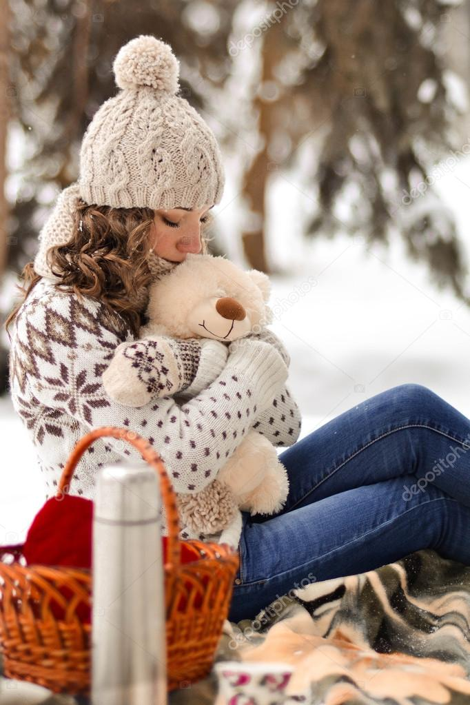 Beautiful nice little and wearing sweater hut and mittens and beautiful nice little and wearing sweater hut and mittens and little girl with a teddy bear in winter forestautiful girlkidbabehuggingembracing altavistaventures Images