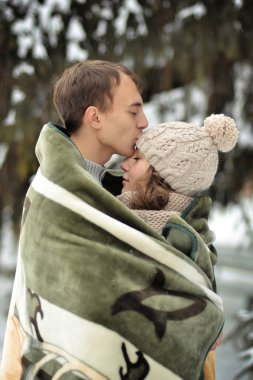 Happy man kissing his beautiful girl on the forehead and covers her blanket. A handsome man kiss on the forehead her beloved, beautiful, pretty girl with sweater, mittens and hut.