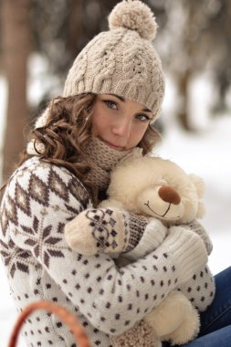 Very cute,lovely,beautiful,attractive.Beautiful, attractive, cute, little girl in winter forest with toy.Beautiful, attractive, cute, little girl in the winter forest with a toy, hold small, tiny, white, beige, soft, fluffy teddy bear, with a bear.