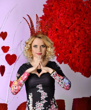 Very beautiful,cheerful, attractive, cute, nice, delightful, adorable, wonderful, notable, well-mannered, well-educated, famous blonde girl, woman, queen, princess with big, red corona, crown, diadem, coroneta . Holiday St. Valentine's Day.