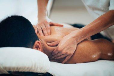 Physical therapist massaging shoulder