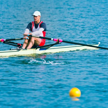 Single scull rowing on lake