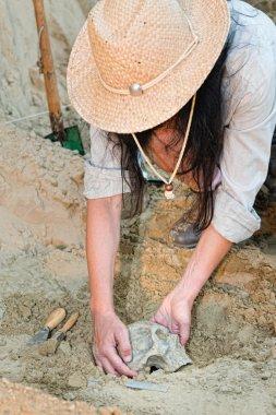 Archaeologist unearthing skull