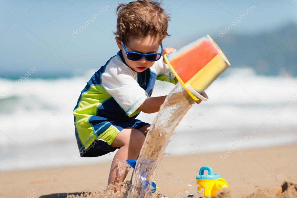 Little boy with bucket on the beach