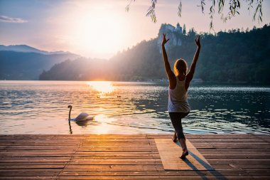 Beautiful woman practicing Yoga by the lake. Sun salutation. Toned image stock vector