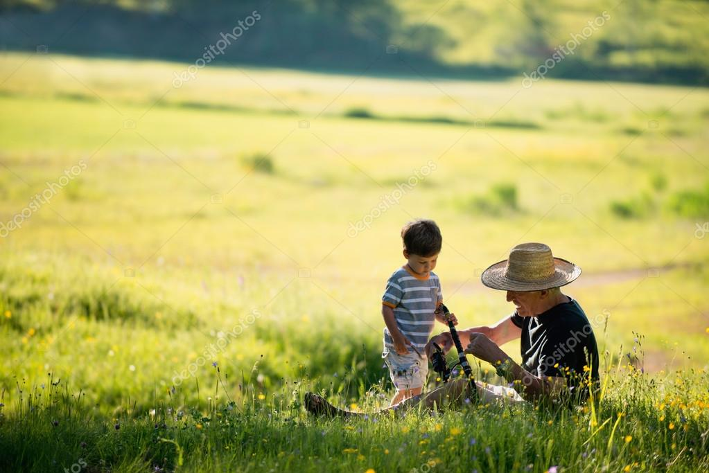 Grandfather and grandson in field