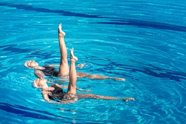 swimming pair performing dance in pool