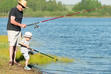 grandson fishing with grandfather