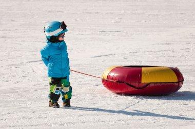 Little boy preparing for snow tubing