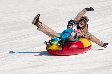 Mother and son snow tubing down hill