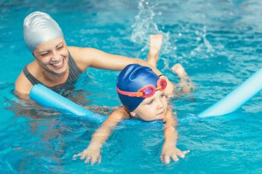 little girl learning to swim with instructor
