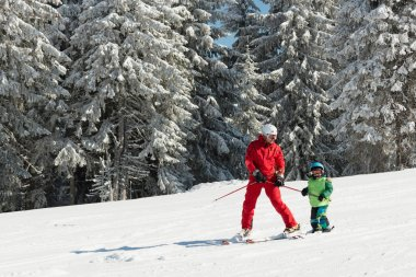 Skiing instructor working with boy