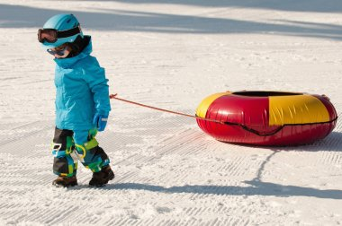 Little boy with snow tube
