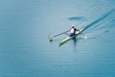 man rowing single scull on lake