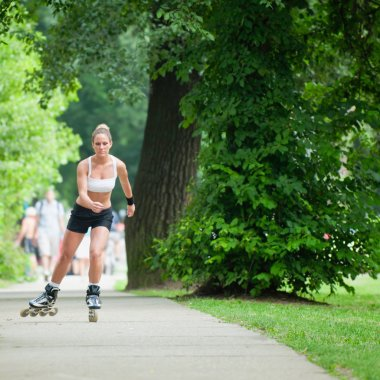 woman roller skating through park