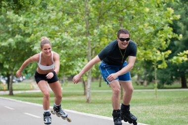 couple roller skating through park