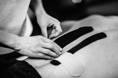 therapist applying kinesio taping on back