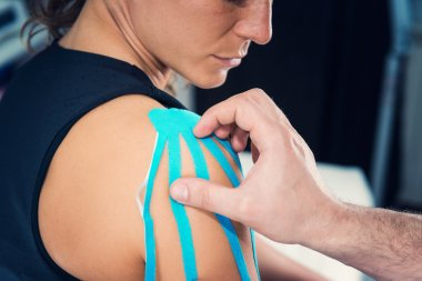 female shoulder with kinesio tape