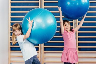 Little girls playing with fitness balls