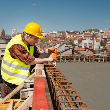 Construction worker tightening wire mesh