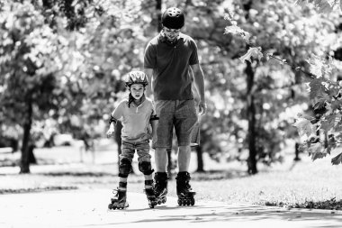father teaching son roller skating