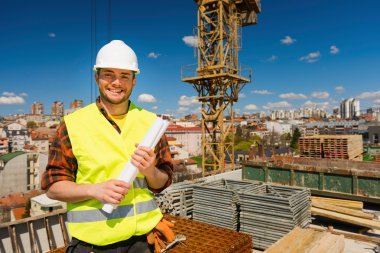 construction worker posing with blueprint