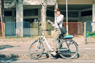 woman with electric bicycle and phone