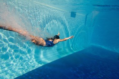 woman glides through water of swimming pool