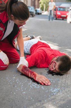 Paramedic with car accident victim on street