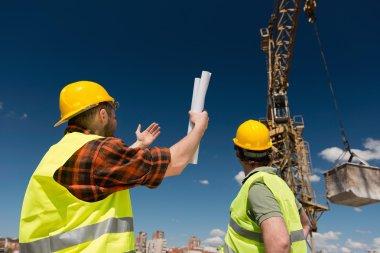 Construction workers over crane