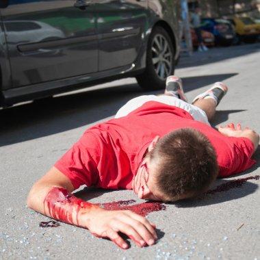 Car accident victim lying on street