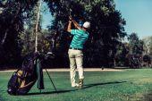 Fotografie Golfer swinging on putting grass