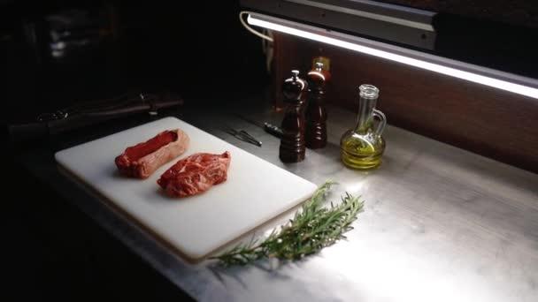 Vaření hovězího steaku doma, hovězí řízek na prkně, šťavnatý steak s grilovacími proužky, šéfkuchař dal rozmarýn na maso