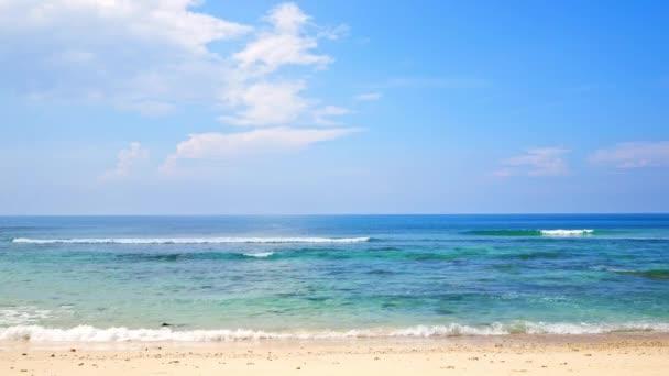 malebný přístav s mořskými vlnami, písečnou pláží a modrou oblohou