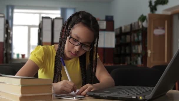 Lány, hosszú haj, szemüveg, működik az iskolai könyvtár.