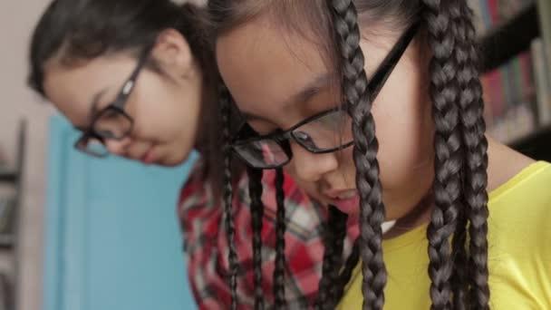 Két nővér, hosszú haj, iskolai könyvtár