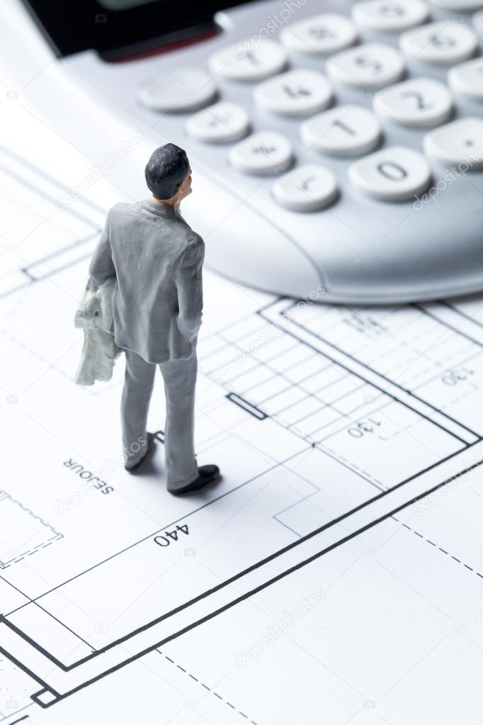 Businessman miniature with calculator on architect blueprint for businessman miniature with calculator on architect blueprint for housing cost stock photo malvernweather Image collections
