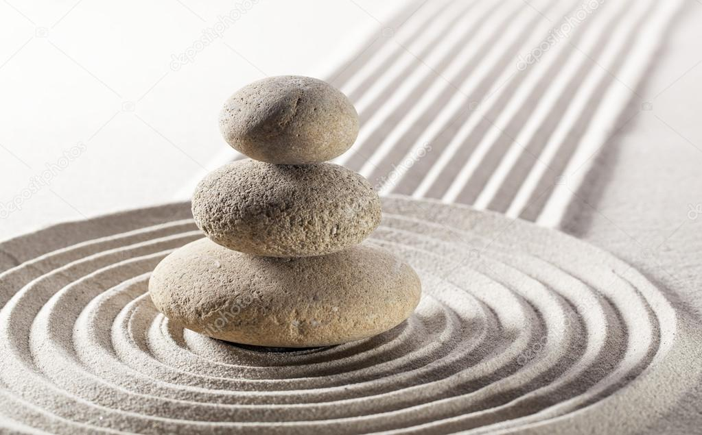 Balanced pebbles in sand for meditation and contemplation