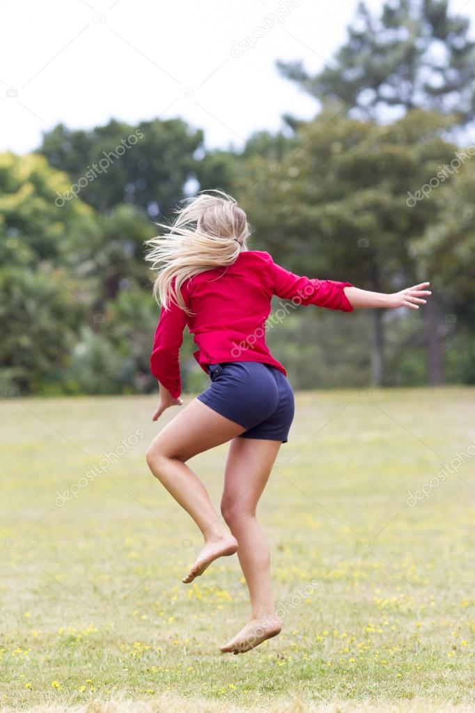 energetic young woman dancing for holiday in green outdoors
