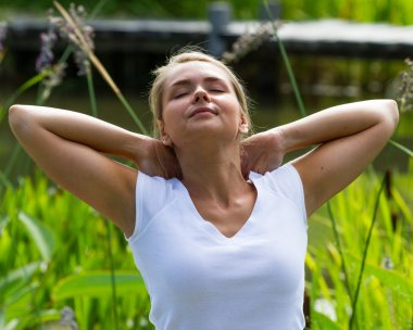 relaxation outdoors - 20s blond girl enjoying relaxing in sun heat in park