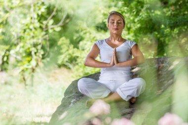 outdoors meditation - zen 20s blond girl meditating on a big stone