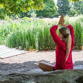 20-as évek szőke lány gyakorló meditáció egy városi parkban